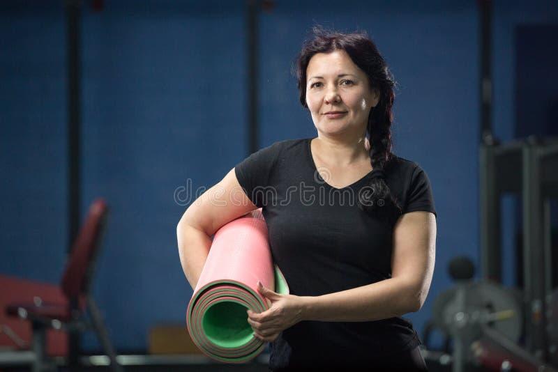 Hogere vrouw bij de gymnastiek die een roze yogamat houden Close-up De ruimte van het exemplaar stock fotografie