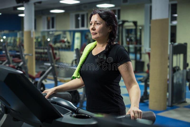 Hogere vrouw bij de gymnastiekgangen op een tredmolen Close-up De ruimte van het exemplaar royalty-vrije stock afbeeldingen