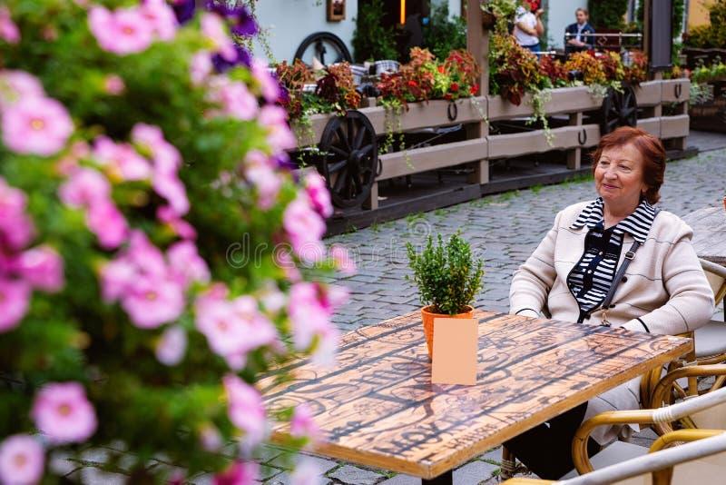 Hogere vrouw bij de koffie van de Terrasstraat in Oude Stad Riga stock foto's