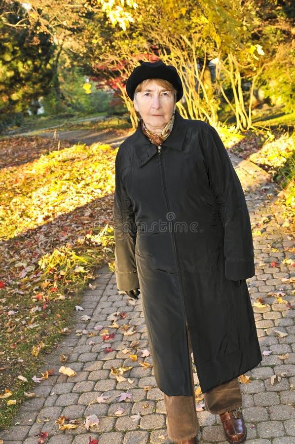 Hogere vrouw in dalingspark stock foto's