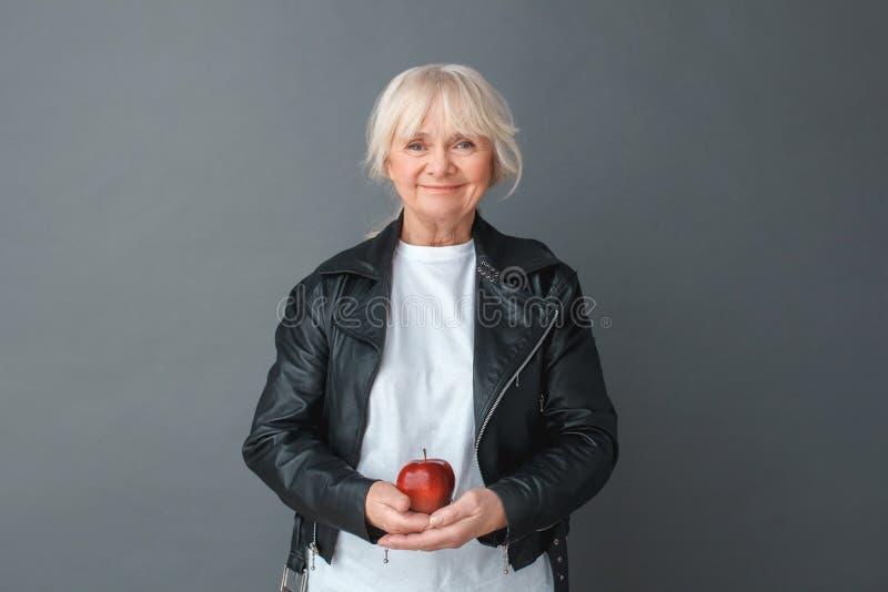 Hogere vrouw in de studio van het leerjasje status geïsoleerd op grijze holdingsappel die camera gelukkige rust kijken royalty-vrije stock foto