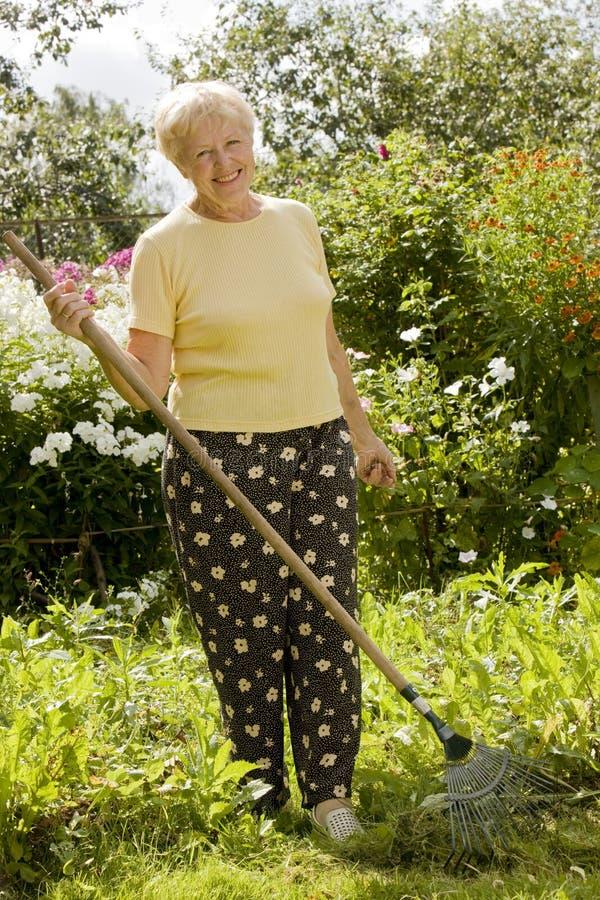 Hogere vrouw in de tuin stock afbeelding