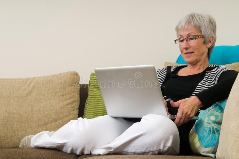 Hogere vrouw die aan laptop werkt stock foto's