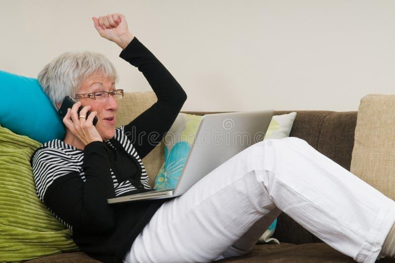 Hogere vrouw die aan laptop werkt stock foto