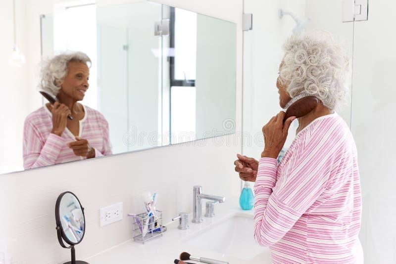 Hogere Vrouw die Bezinning in Badkamersspiegel het Borstelen Haar bekijken royalty-vrije stock foto's