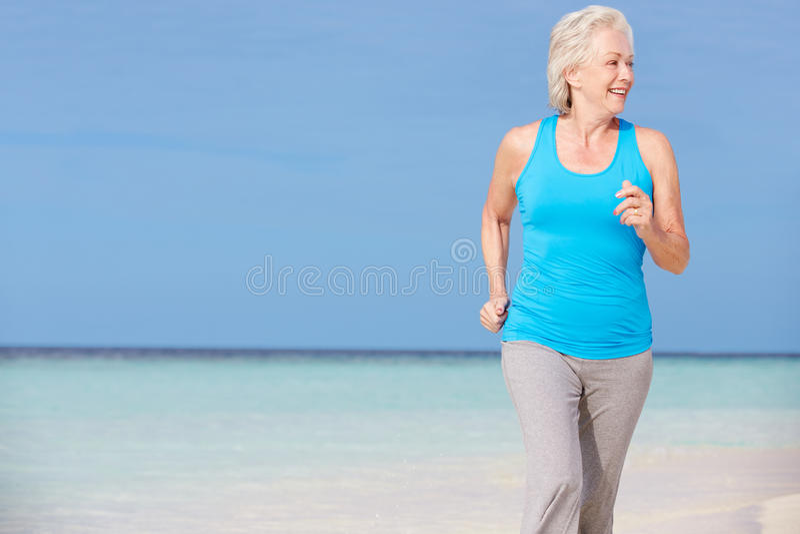 Hogere Vrouw die op Mooi Strand lopen royalty-vrije stock afbeelding