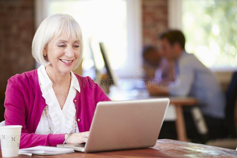 Hogere Vrouw die bij Laptop in Eigentijds Bureau werken stock afbeelding