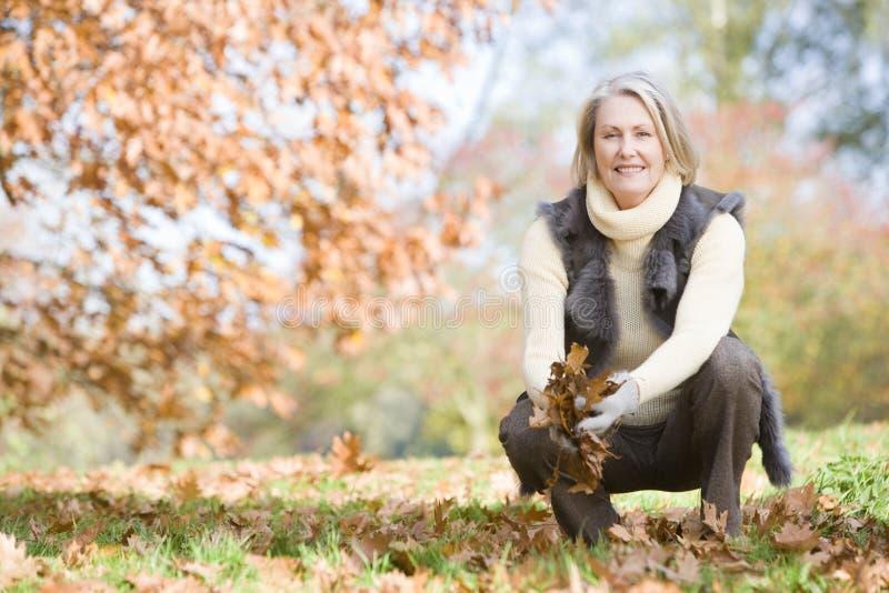 Hogere vrouw die bladeren op gang verzamelt royalty-vrije stock foto's