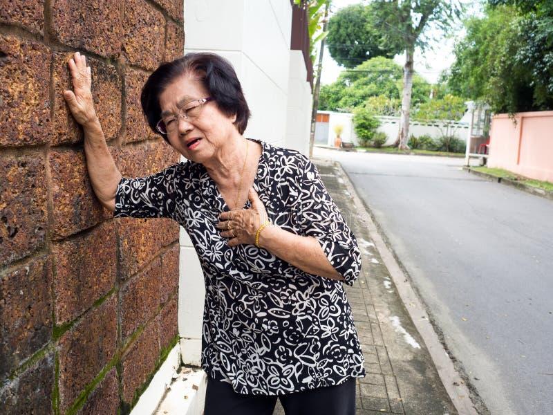 Hogere vrouw die borstpijn en haar holdingsborst wegens hartinfarct hebben Hartaanvalconcept stock afbeelding