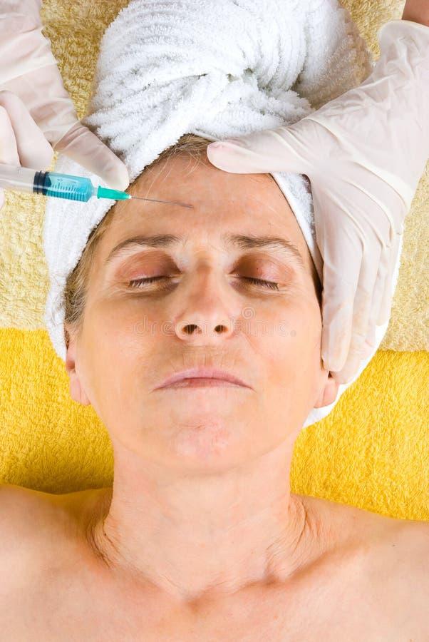 Hogere vrouw die botox injectie krijgt stock afbeelding