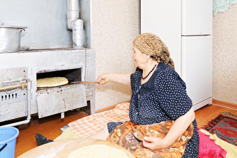 Hogere vrouw die brood zetten in oven royalty-vrije stock afbeeldingen