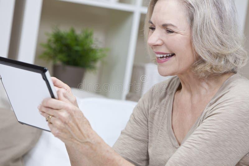 Hogere Vrouw die de Computer van de Tablet met behulp van stock afbeelding