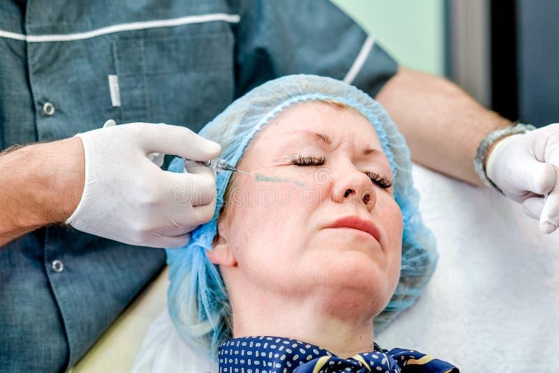 Hogere vrouw die de injectie van de huidzorg krijgt stock afbeeldingen