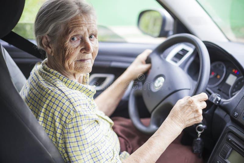 Hogere vrouw die een auto drijft stock afbeeldingen