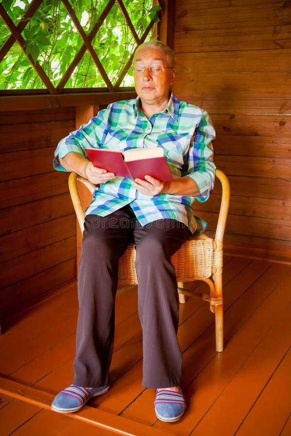Hogere vrouw die een boek leest royalty-vrije stock afbeelding