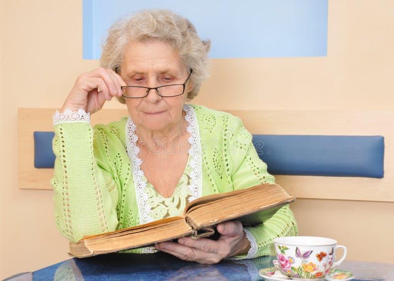 Hogere vrouw die een groot boek thuis lezen royalty-vrije stock afbeeldingen
