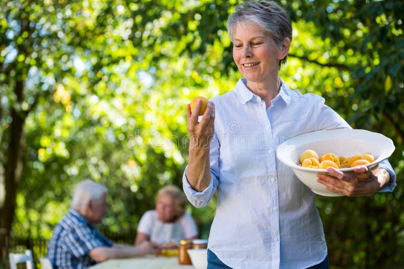 Hogere vrouw die een kom van abrikoos in tuin houden royalty-vrije stock foto