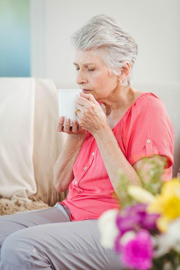 Hogere vrouw die een kop van koffie ruiken stock foto's