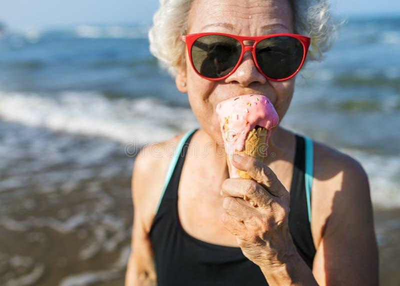 Hogere vrouw die een roomijs eten stock afbeeldingen