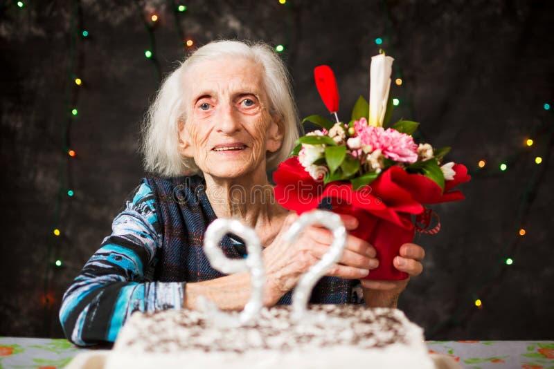 Hogere vrouw die een verjaardagsgeschenk houden royalty-vrije stock afbeelding