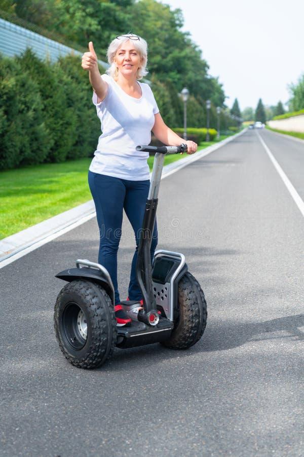 Hogere vrouw die elektrische persoonlijke vervoerder gebruiken royalty-vrije stock afbeeldingen
