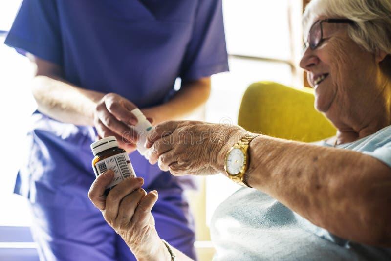 Hogere vrouw die geneeskunde van de verpleegster nemen stock foto's