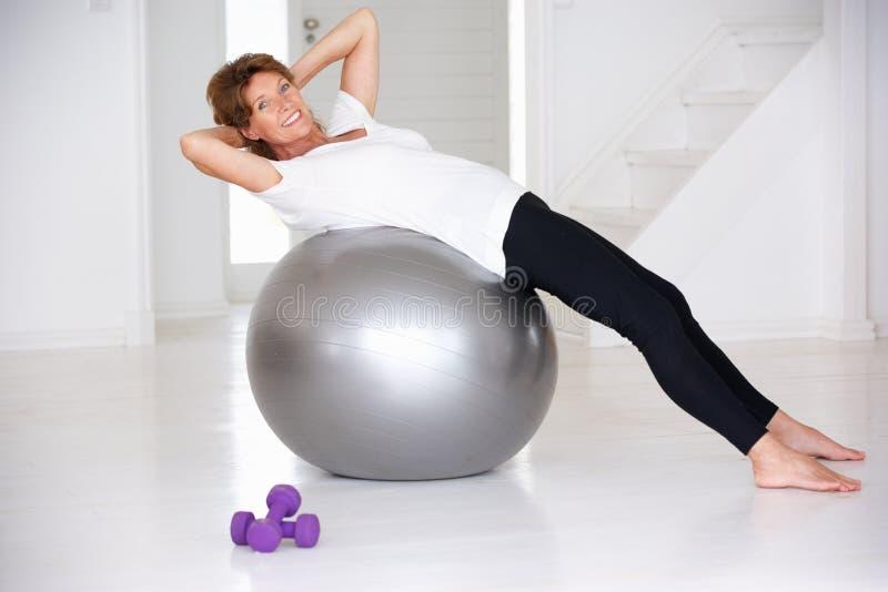Hogere vrouw die gymnastiekbal gebruikt stock afbeelding