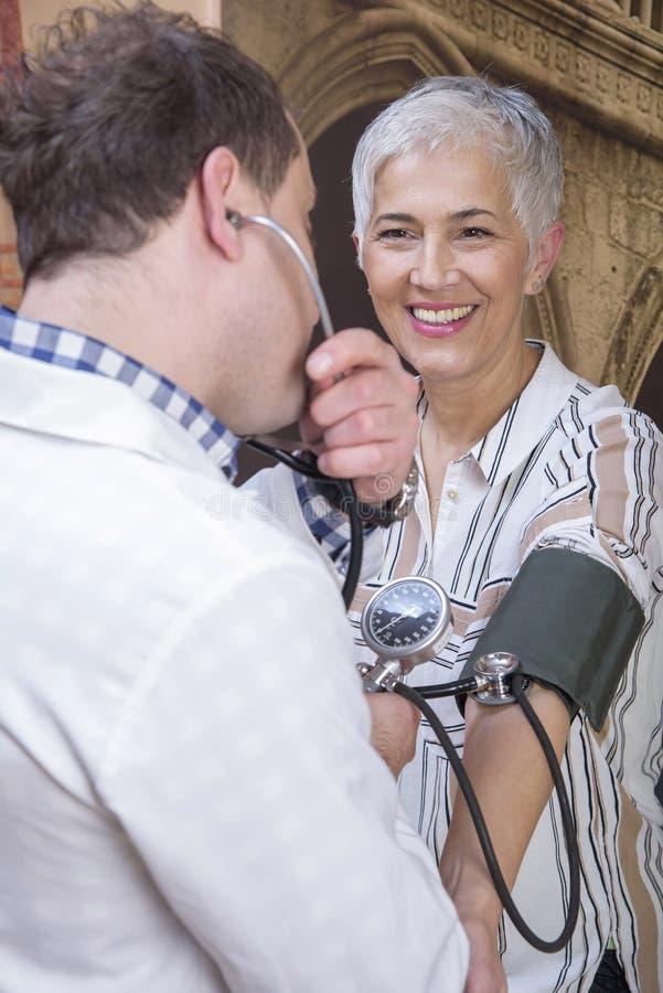 Hogere vrouw die haar bloeddruk controleren bij de kliniek royalty-vrije stock afbeelding