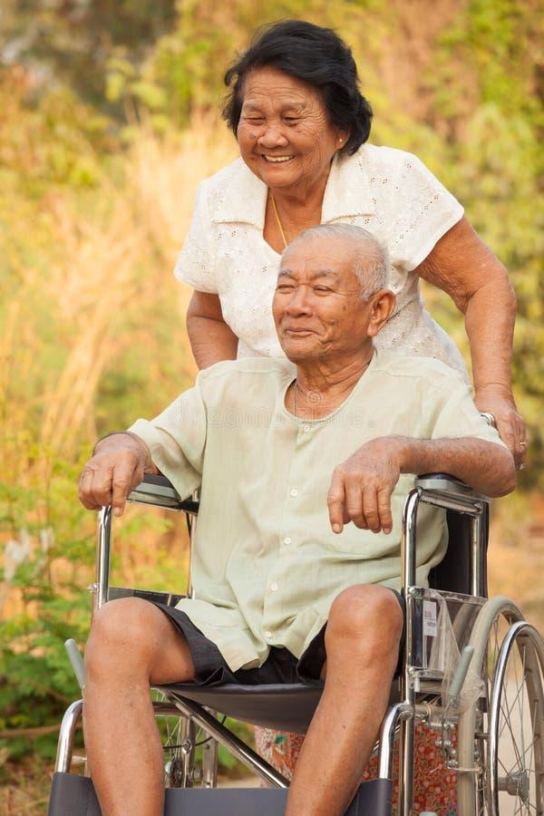 Hogere vrouw die haar gehandicapten hasband op rolstoel duwen royalty-vrije stock fotografie