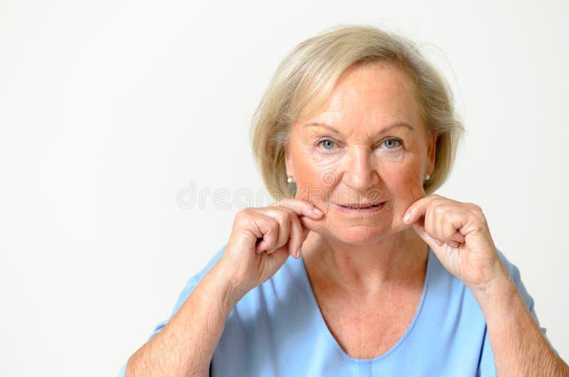 Hogere vrouw die haar gezicht, effect toont van het verouderen stock foto