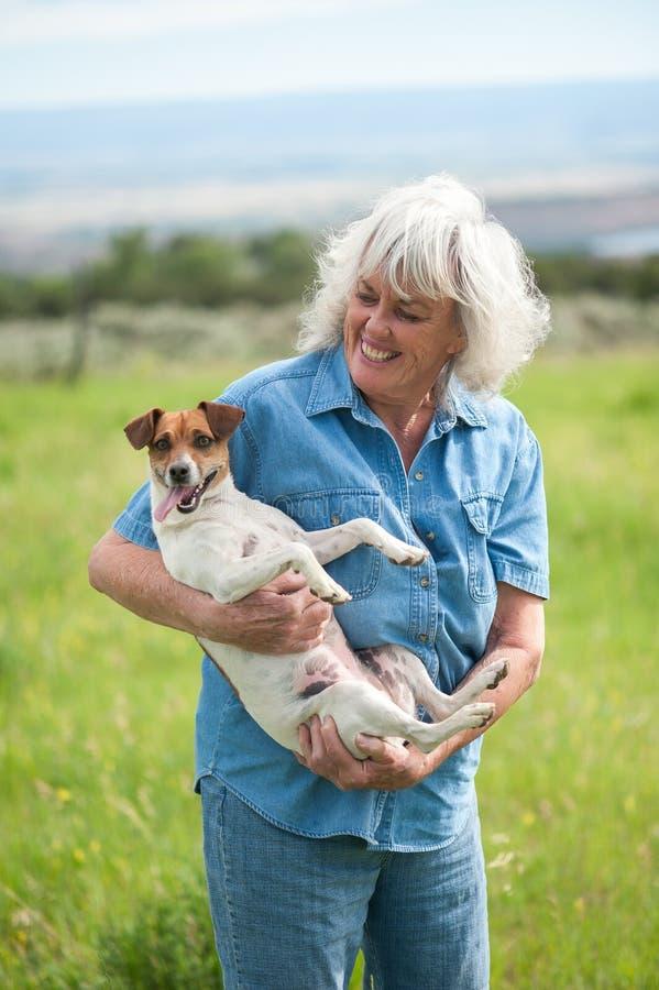 Hogere Vrouw die haar Huisdierenhond dragen royalty-vrije stock afbeelding