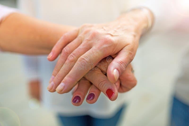 Hogere vrouw die handen stapelen stock foto