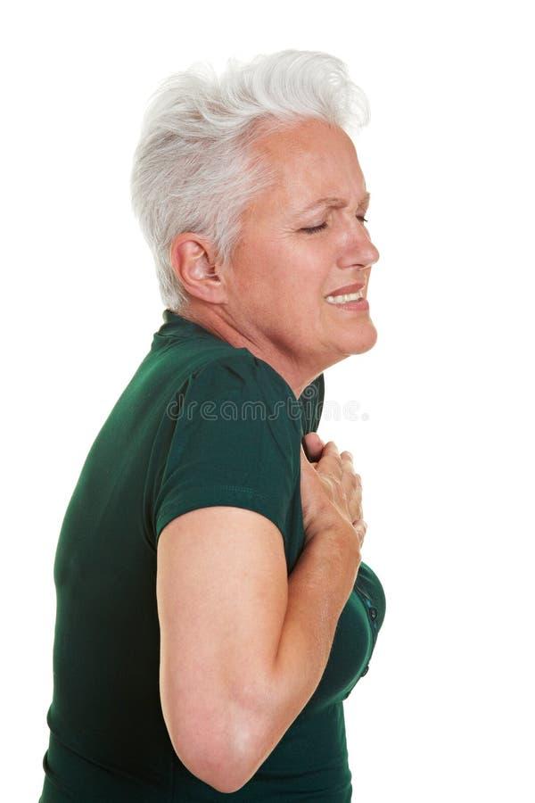 Hogere vrouw die hartpijn heeft stock afbeeldingen