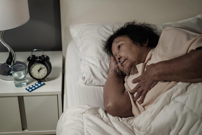 Hogere vrouw die hartprobleem in een bed hebben stock foto