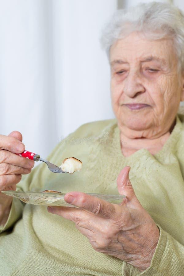 Hogere vrouw die iets eten royalty-vrije stock afbeeldingen