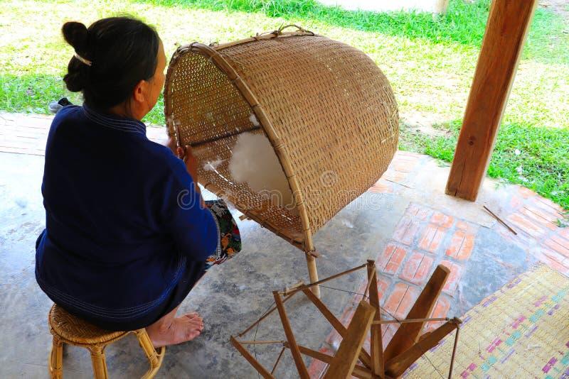 Hogere vrouw die katoen voor het spinnen voorbereiden aan het inpassen stock afbeelding