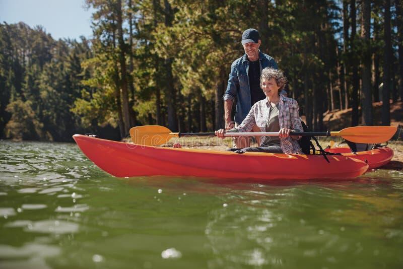 Hogere vrouw die kayaking lessen van een man krijgen royalty-vrije stock fotografie