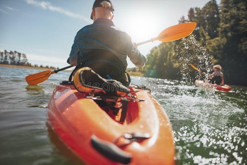 Hogere vrouw die kayaking lessen van een man krijgen stock afbeeldingen