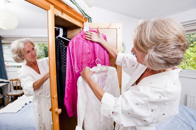 Hogere vrouw die kleding thuis kiezen van kast stock fotografie