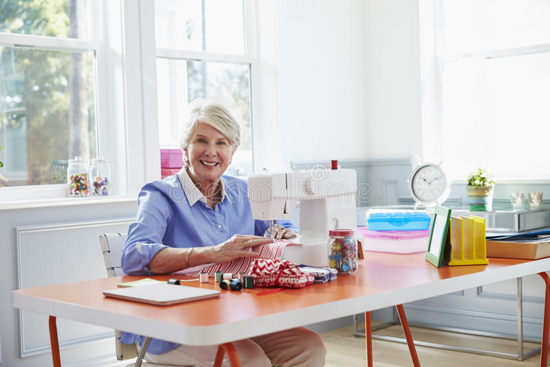 Hogere Vrouw die Kleren maken die Naaimachine thuis met behulp van stock foto's