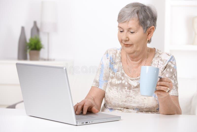 Hogere vrouw die laptop computer met behulp van stock foto's