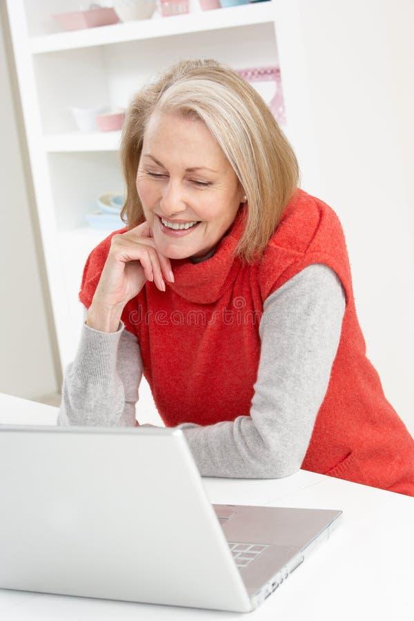 Hogere Vrouw die Laptop thuis met behulp van stock foto's