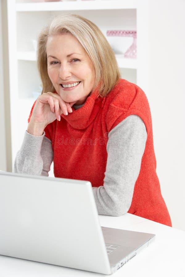 Hogere Vrouw die Laptop thuis met behulp van royalty-vrije stock foto's