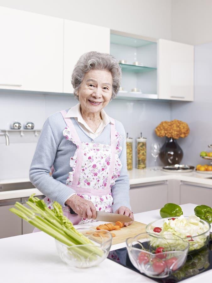 Hogere vrouw die maaltijd in keuken voorbereidt royalty-vrije stock foto's