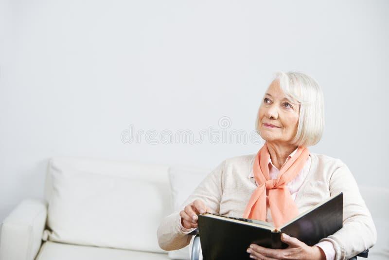 Hogere vrouw die met boek peinzend kijkt royalty-vrije stock foto's