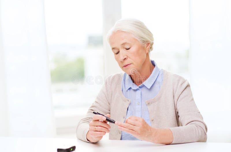 Hogere vrouw die met glucometer bloedsuiker controleren stock foto