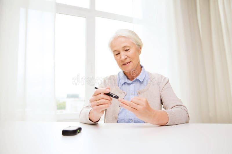 Hogere vrouw die met glucometer bloedsuiker controleren stock foto's
