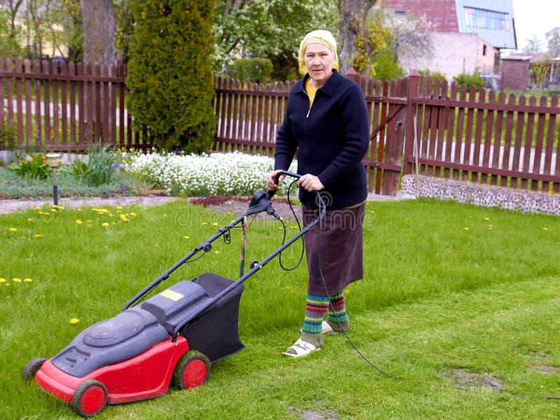 Hogere vrouw die met grasmaaimachine werkt stock afbeelding