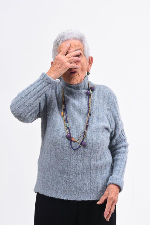Hogere vrouw die met hand op gezicht op witte achtergrond gluren royalty-vrije stock foto's