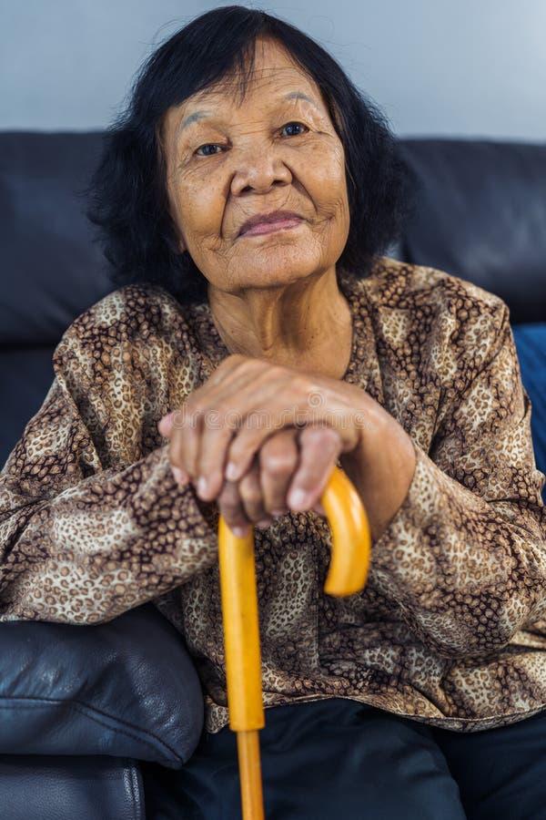 Hogere vrouw die met houten riet glimlachen royalty-vrije stock foto